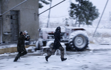 Free Syrian Army fighters run as they play with snow in Khan Tuman, Aleppo