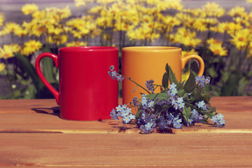 coffee break with a summer mood/ Red and orange mug with a blue bouquet of flowers on a street table
