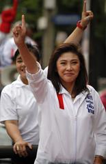 Yingluck Shinawatra shows her trademark gesture as she campaigns through streets of Bangkok