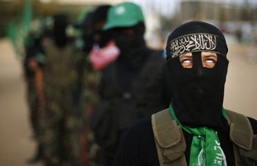 masked young Hamas member marches during an anti-Israel protest in the central Gaza Strip