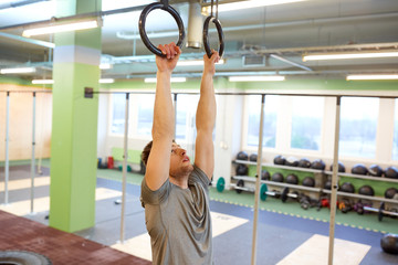 man exercising and doing ring pull-ups in gym