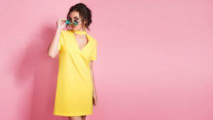 Beautiful girl in colorful clothes wearing sunglasses posing on pink background in studio.