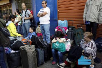 People wait to try to cross the Simon Bolivar international bridge into Colombia, in San Antonio del Tachira