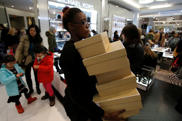 An attendant carries boxes of shoes during early Black Friday sales at Macy's Herald Square in Manhattan, New York, U.S.