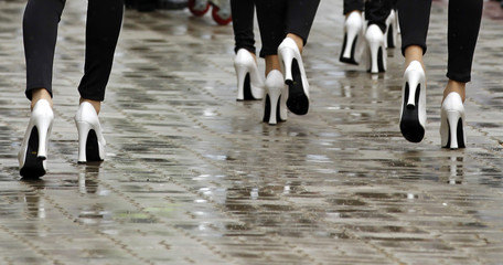 The high heel shoes of grid girls are seen as they walk in the rain ahead of the South Korean F1 Grand Prix at the Korea International Circuit in Yeongam