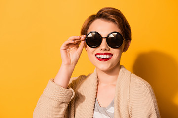 Close up studio shot of cheerful young beautiful woman with short hair and red lips touching sunglasses