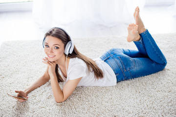 Pretty young lady is listening to the music with headphones at home lying on her belly on the white carpet