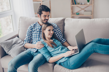 So easy! Excited beautiful happy couple is doing online shopping in internet. They are indoors at home on cozy couch in casual clothes, relaxing and buying goods easily