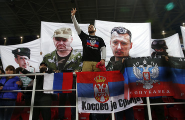 Russia's fans display flags of Russia, Serbia, the self-proclaimed Donetsk People's Republic and banners with portraits of pro-Russian rebel leaders during their Euro 2016 Group G qualifying soccer match against Moldova at the Otkrytie Arena in Moscow