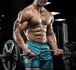 Przystojny mężczyzna z dużymi mięśniami, pozuje przy kamerą w gym