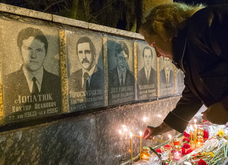 A woman lights candles at a memorial, dedicated to firefighters and workers who died after the Chernobyl nuclear disaster, during a night service in Slavutych