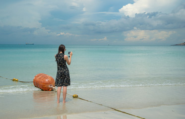 Woman photographed with a smartphone at Nam Sai Beach, Chonburi, Thailand