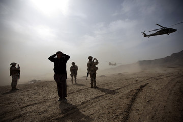 Two helicopters escorting U.S. Secretary of Defense Gates take off after a visit to Camp Black Horse in Kabul