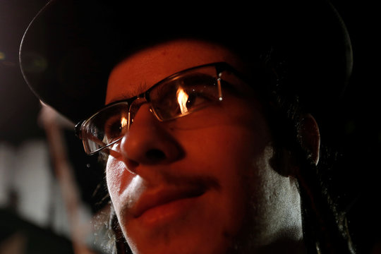 A bonfire is reflected in the eyeglasses of an Orthodox Jew of the Satmar Hasidim during a celebration of the Jewish holiday of Lag Ba'Omerr in the village of Kiryas Joel