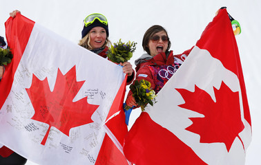 Winner Canada's Dara Howell and compatriot and third-placed Kim Lamarre celebrate with Canadian flags after women's freestyle skiing slopestyle finals at the 2014 Sochi Winter Olympic Games in Rosa Khutor
