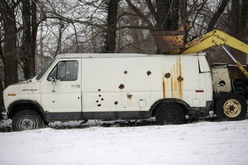An older Ford van with holes and rust spots sits in the yard next to a tractor in Detroit