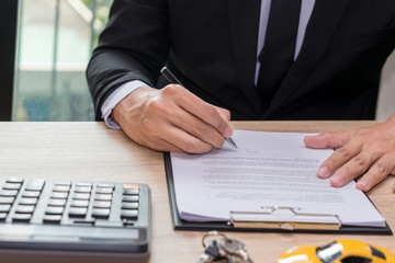 Businessman signing car loan agreement contract with car key and calculator on wooden desk.