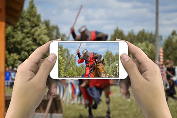 Hands taking photo of knight on horse by smartphone