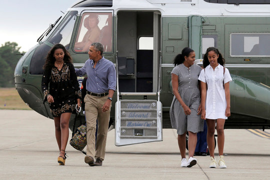 U.S. President Barack Obama, U.S. first lady Michelle Obama and their daughters Malia and Sasha board Air Force One at Cape Cod Coast Guard Air Station in Buzzards Bay, Massachusetts