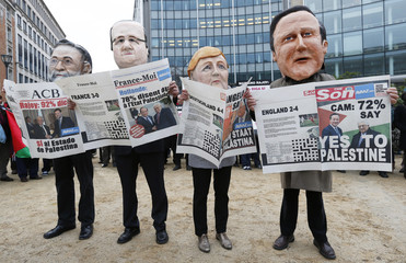 Activists wearing masks depicting Spanish PM Rajoy, French President Hollande, German Chancellor Merkel and Britain's PM Cameron during a protest in Brussels