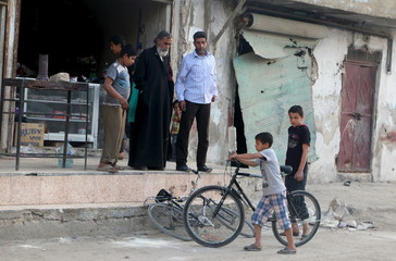 A boy pushes his bicycle near damaged shops in al-Jazmati neighbourhood of Aleppo