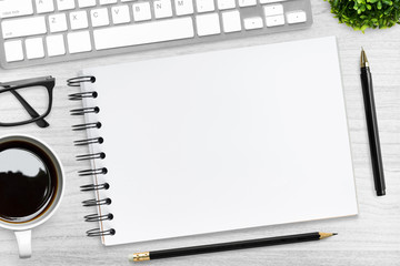 Blank notebook with pen on top of wood table with coffee and office supplies. Top view, flat lay.
