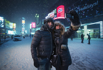 People stop and take picture in the snow in Times Square in New York