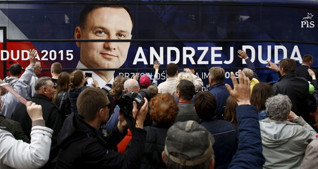 Supporters wave hands as Andrzej Duda, presidential candidate of the conservative opposition Law and Justice (PiS) party leaves by bus after his election meeting in Radziejow near Inowroclaw