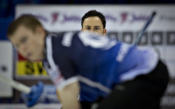 Scotland skip Murdoch watches the line of his shot over teammate Andrews during their page playoff game at the World Men's Curling Championships in Victoria