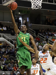 Oregon's Damyean Dotson drives to the basket against Oklahoma State's Markel Brown during their NCAA basketball tournament game in San Jose