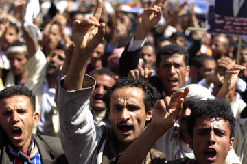 Anti-government protesters shout slogans as they march during a demonstration to demand the ouster of Yemen's President Ali Abdullah Saleh in Sanaa