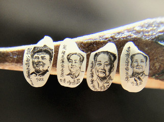 Miniature portraits of former Chinese Chairman Mao on grains of rice, created by Taiwanese artist Chen, are displayed on a pencil in Taipei