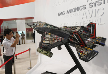 A visitor takes a picture of a miniature fighter jet made of computer parts and tools at Aviation Expo China 2013 in Beijing
