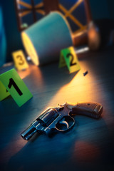 dramatic lit crime scene with gun and markers on the floor