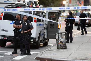NYPD officers stand near the site of an explosion in New York