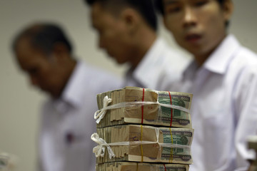 Stack of 1000 kyat banknotes is seen, as employees count money at Yoma Bank in Yangon