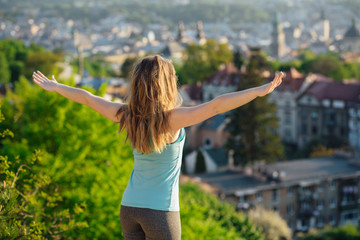 Back view portrait of a happy beautiful woman breathing and raising arms on the hill in sunny summer day.