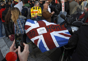 Iberia workers hold a mock coffin covered in a replica of the British flag as they protest in Barcelona