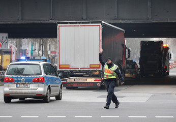 A policeman stops traffic as the truck which ploughed into a crowded Christmas market is towed in Berlin