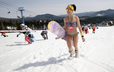 "A woman in a bikini walks up to the start position of a ""downhill ski and snowboard descent in swimwear"" event on Mount Zelyonaya, at a ski resort near the town of Sheregesh in the Siberian Kemerovo region"