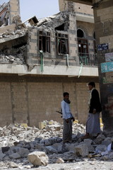 Houthi militants stand outside the Houthi-controlled headquarters of the Yemeni army after it was hit by Saudi-led air strikes in the capital Sanaa