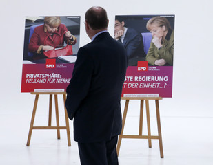 Steinbrueck SPD candidate for German Chancellor in the upcoming general election looks at election campaign posters during their official presentation in Berlin