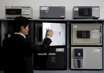 A staff opens a safety deposit box during a photo opportunity at a security showroom in Tokyo