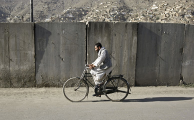 Afghan man raids his bicycle in front of security barriers in Kabul