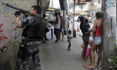 A police officer takes up position during an operation at the Mare slums complex in Rio de Janeiro