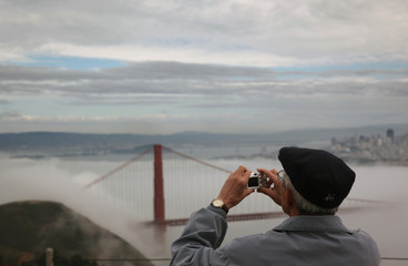 A man takes a photograph of the fog shrouded Golden Gate Bridge from the Marin Headlands in Sausalito