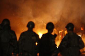 Lebanese soldiers stand in front of bunt tires lit by Sunni Muslim supporters of Lebanon's caretaker Saad al-Hariri