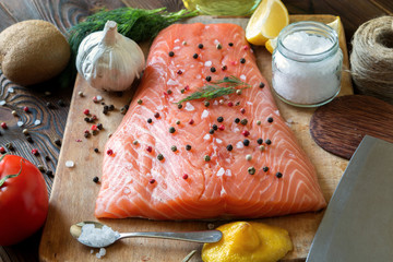 Fresh delicious salmon fillet with aromatic herbs, spices, garlic, lemon on dark background. Top view. Closeup.
