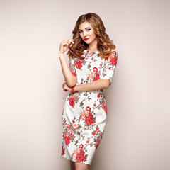 Blonde young woman in floral spring summer dress. Girl posing on a white background. Summer floral outfit. Stylish wavy hairstyle. Fashion photo. Glamour lady with sunglasses
