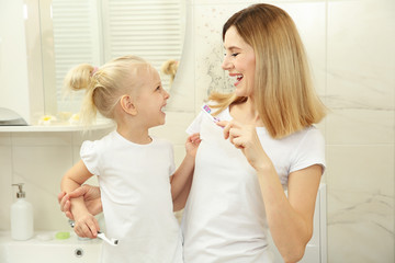 Happy little girl with her mother brushing teeth in bathroom